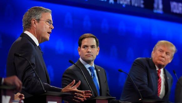 Marco Rubio, center, and Jeb Bush, left, argue a point