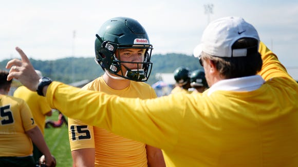 Reynolds' quarterback Alex Flinn talks with a coach during the WNC FCA 7 on 7 competition at Erwin High July 10, 2018.