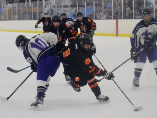 James Carrier (8) slips around New Rochelle defenseman Nick Ramondelli (10) in the first period of a Section 1 playoff game at the Ice Hutch. The Tigers forward scored to make it a 1-1 game.
