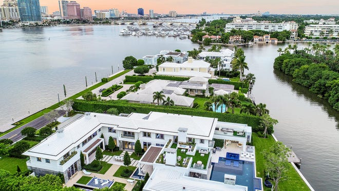 In the foreground, a California contemporary-style house at 520 Island Drive on Everglades Island in Palm Beach has a courtyard design and waterfront on two sides.  Priced at $45 million, the house is under contract.