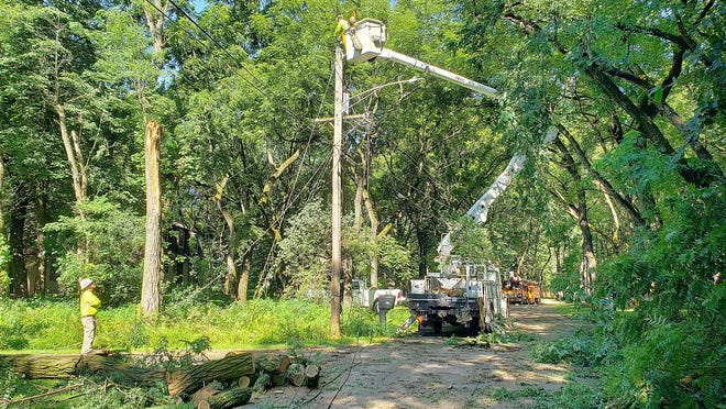 Crews from J F Electric from Edwardsville restore power in the Gladewood subdivision on Tuesday in Freeport. Numerous trees downed power lines during a Monday afternoon storm.