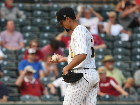 Southern Miss pitcher Nick Sandlin looks over the baseball