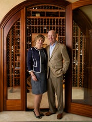 Bev and Art Cherry in front of their custom built wine cellar in their Port Royal home in Naples.