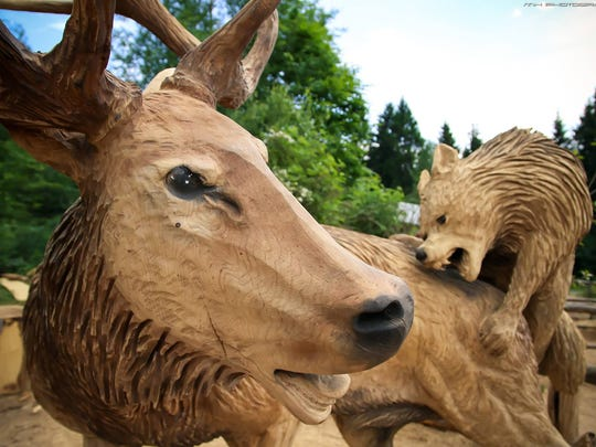 Dennis Beach's carving of a life-size elk being attacked by wolves won first place in the world championship of woodcarvers.