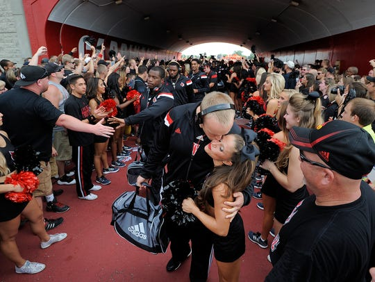 Former Louisville player Josh Appleby kisses his then-girlfriend (and current wife) Leslie Courtney, a U of L cheerleader, prior to a 2014 game against Miami.