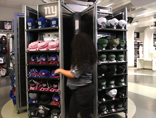 A MetLife Stadium worker flips the hat display in the