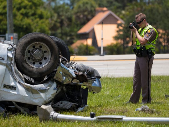 A Florida Highway Patrol trooper photographs the scene