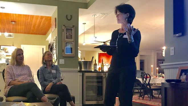Lisa Dougherty, right, talks with Marcia Luhn, left, Suzie Black and other Dining for Women guests about Asia Initiatives.