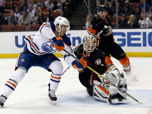 In this Wednesday, March 22, 2017, photo, Edmonton Oilers center Connor McDavid, left, scores against Anaheim Ducks goalie Jonathan Bernier, center, with defenseman Cam Fowler, right, watches during the first period of an NHL hockey game in Anaheim, Calif. The NHL's coaching carousel is paying off for playoff-starved franchises in Toronto, Edmonton and Columbus. With the season wrapping up on Sunday, the Maple Leafs' Mike Babcock, Oilers' Todd McLellan and Blue Jackets' John Tortorella have emerged as coach of the year candidates. (AP Photo/Alex Gallardo)