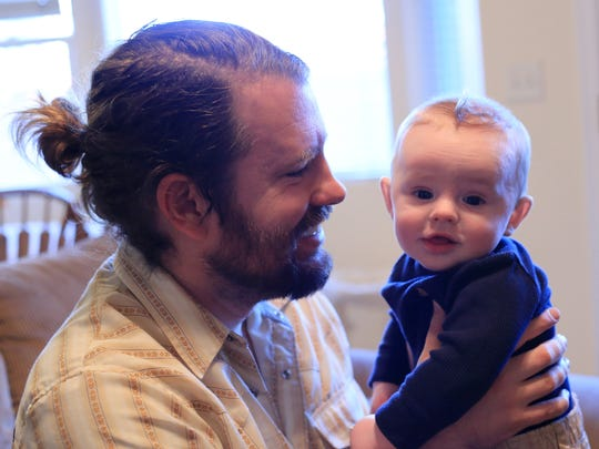Jared Buhanan-Decker plays with his 5-month-old son, JJ, on Nov. 17 at their home in St. George.