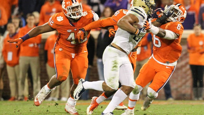Pitt running back James Conner runs by Clemson linebacker Dorian O'Daniel (6) and defensive tackle Christian Wilkins (42) to score a 20-yard touchdown during the fourth quarter on Saturday at Memorial Stadium.