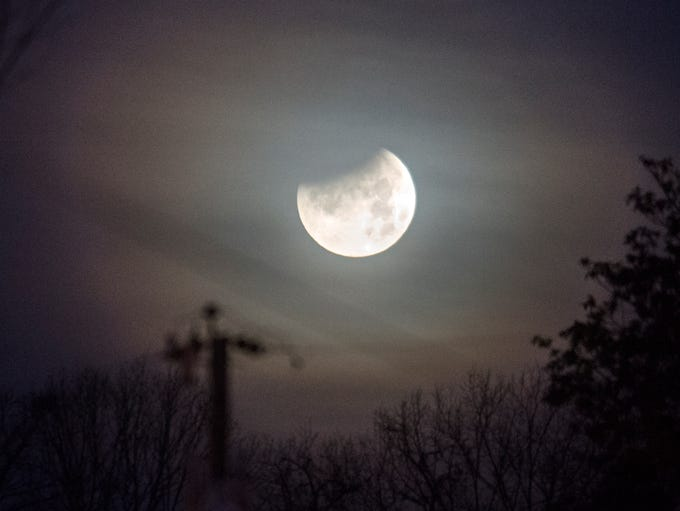 A partially eclipsed supermoon sets in Bearden, Wednesday,