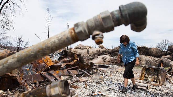 Vanessa Purdy looks through the ashes of what was her home in the Glen Ilah neighborhood of Yarnell, Monday, August 5th, 2013, five weeks after the Yarnell Hill Fire moved through the area, destroying homes and disrupting the lives of hundreds of residents.