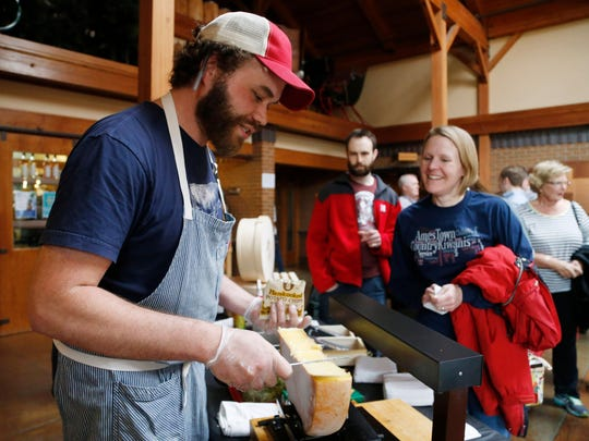 C.J. Bienert with The Cheese Shop scrapes off the top melted layer on a wheel of raclette cheese Saturday, April 1, 2017, as he serves up his take on a walking taco at the Festival of Cheese at Living History Farms in Urbandale