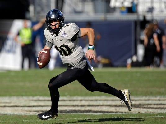 FILE - In this Dec. 2, 2017, file photo, Central Florida quarterback McKenzie Milton scrambles during the second half of the American Athletic Conference championship NCAA college football game against Memphis in Orlando, Fla. Milton has a lot of Baker Mayfield in his game, with an ability to turn a broken play into a huge gain. He will have a new coach next year in Josh Heupel, but theoretically that should not slow down the Knights' offense. (AP Photo/John Raoux, File)