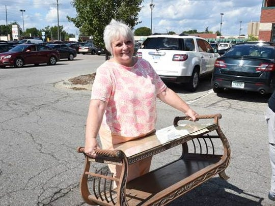 Michele Jarrait of Garden City is all smiles as she gets ready to load her antique coffee table that was purchased at the Lucky Squirrel