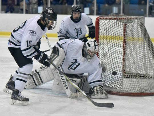 Teaming up to stave off a Livonia Stevenson scoring chance are Plymouth goalie Brendan Olepa (1), junior forward Jeffrey Koviak (10) and senior defenseman Andrew Garby (6).