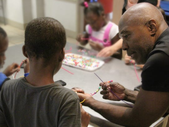 Nick Cave teaches children how to make beaded blankets.