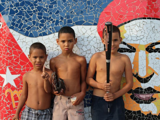Cuban youth pose in front of a street mosaic of Venezuelan