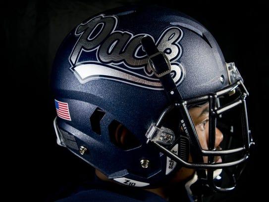 Malik Reed shows off Nevada's new helmets.
