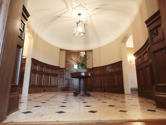 The foyer has a plaster dome ceiling with raised oak