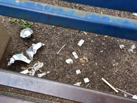 Used needles and other signs of drug use under a bench