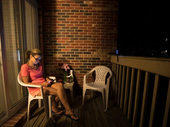 On July 16, Lizzie Hamblin looks at her phone at her Crescent Springs apartment. Her son, Scotty, was missing.