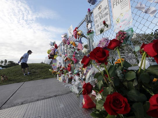 Flowers adorn a fence at a makeshift memorial outside