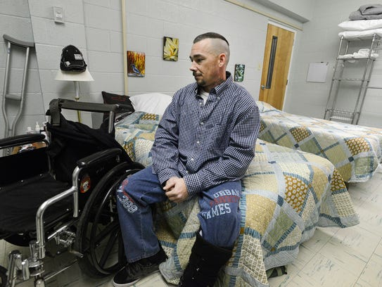 David Webb, 39, sits on the bed provided to him for