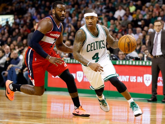 Isaiah Thomas (4) drives past John Wall (2) during