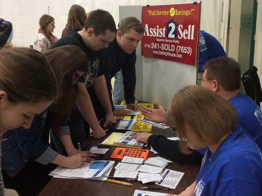 Local business employees help students to get an idea of what their expenses might be.