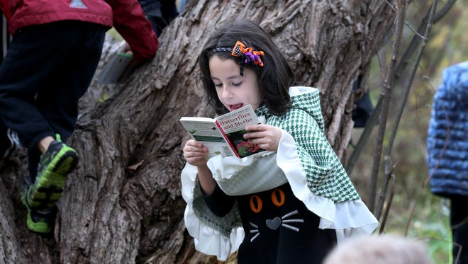 First-grader, Irene Sesnieat, looks through a book of animals while exploring the outdoor classroom at Lima Primary School.