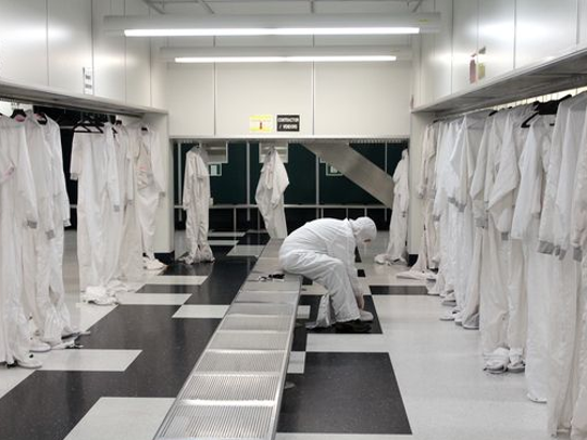 """Suiting up for a tour of IBM Burlington's fab in Essex Junction ends by pulling on special boots to complete the """"bunny suit"""" everyone must wear inside the clean room."""