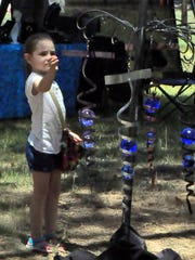 A little girl is intrigued with a mobile hanging at a vendor's tent at the Two Rivers Arts and Crafts Show.