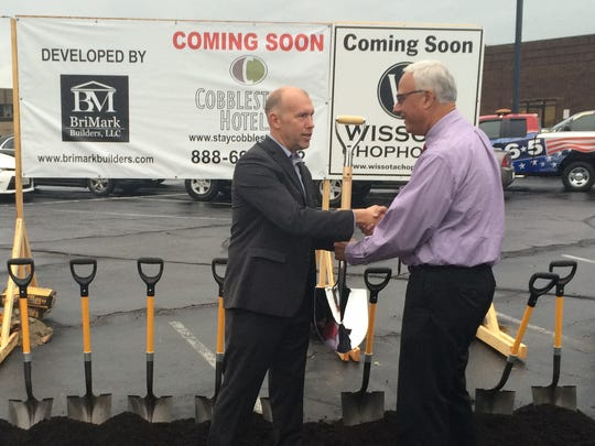 Brian Wogernese, president of Cobblestone Hotels, hands a shovel to Todd Kuckkahn, executive director of the Portage County Business Council, during a groundbreaking for the new Cobblestone Hotel in downtown Stevens Point on Sept. 22, 2016.