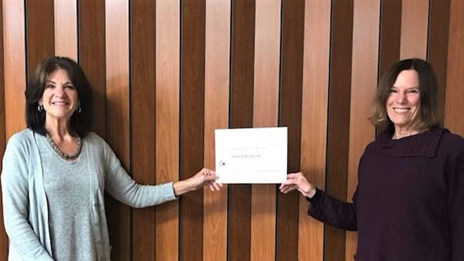 Brix Challenge coordinator Patti Pasquesi-Nemec (left) and HSMC President Bonnie Smith-Skripps (right) stand with the award of $18,847 raised through this year's Brix Challenge.