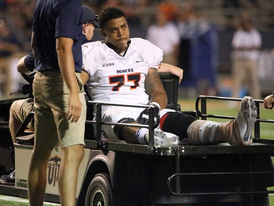 UTEP offensive lineman Greg Long is led off the field