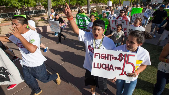 Protesters march through ASU during a rally to raise the minimum wage to $15 in Tempe April 15, 2015.