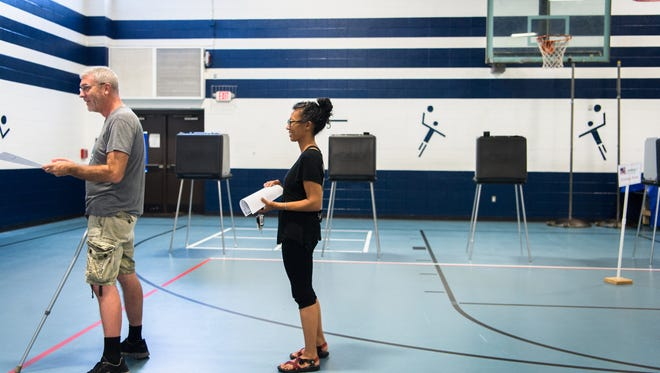 Voters wait in line to cast their ballots in the gymnasium at Vance Elementary School on Tuesday, October 10, 2017.