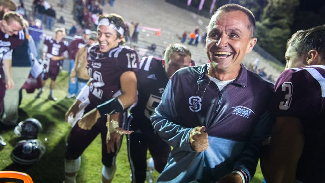 Swain County football head coach Neil Blankenship laughs after having a water cooler dumped on him after their win over Murphy Friday, October 20, 2017.
