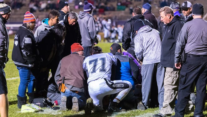 Family, emergency personnel and fellow players gather around Robbinsville's Elijah Wachacha after he was knocked unconscious during a play in their game against Mitchell Friday, November 24, 2017.