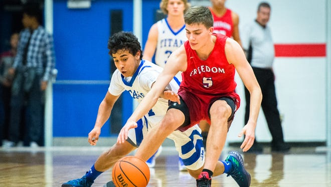 McDowell's JC Olivo and Freedom's Fletcher Abee dive after a loose ball during their game Tuesday, January 16, 2018.