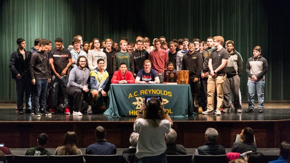 Talon James, of AC Reynolds high school who plans on attending University of Richmond, poses for photos with his football teammates at the signing day ceremony on national signing day Wednesday, February 7, 2018.