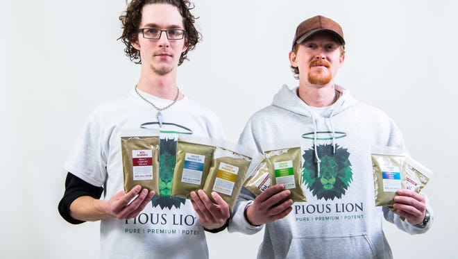 Matt McGrory and Ryan Leonard, owners of Pious Lion brand kratom, holding pouches of several of the strains they offer.