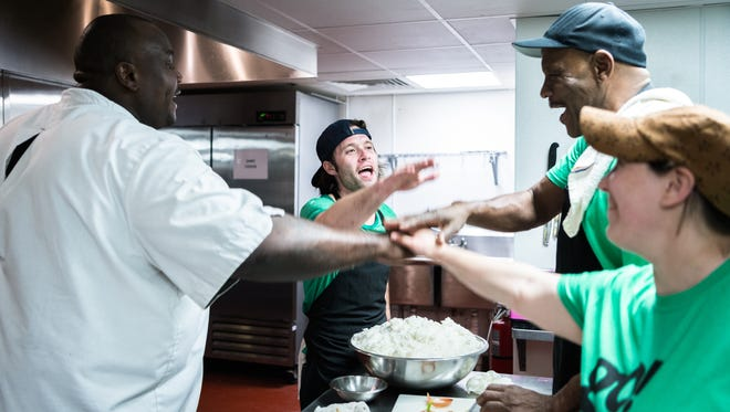 Executive chef Gene Ettison, and Green Opportunities' Kitchen Ready program students Daniel Burroughs, William Raines and Tanichka Givvens put their hands in for a cheer before their showcase dinner at the Southside Kitchen in Asheville Thursday, February 22, 2018.