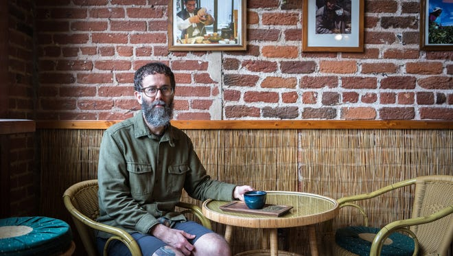 Andrew Snavely, owner of Dobra Tea, at the downtown location with a cup of their CBD hemp latte simmered in coconut or cow milk with local honey.