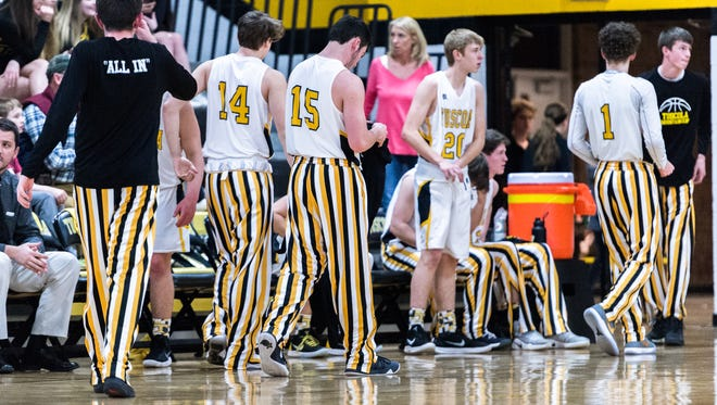 The Tuscola high school boys basketball team warms up wearing their pin striped warm up pants.