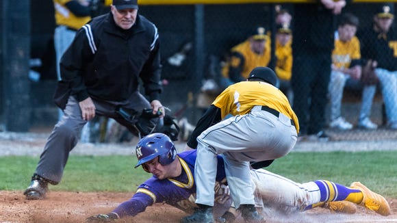 North Henderson's Riley Johnson dives safely across home plate avoiding the tag of Tuscola's Jarrett Penland during their game Friday, March 9, 2018. North Henderson defeated Tuscola 5-2 in 12 innings.