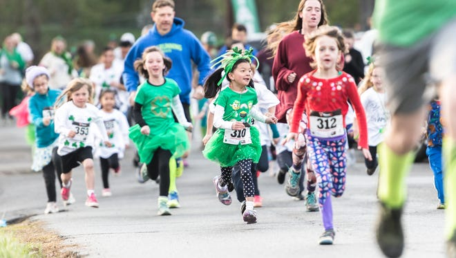Young runners in the 12th annual Asheville Shamrock fun run, race down Culvern Street Saturday, March 17, 2018. This year's run benefited the O'Brien and William Edward Gibbs Memorial Scholarship Fund.