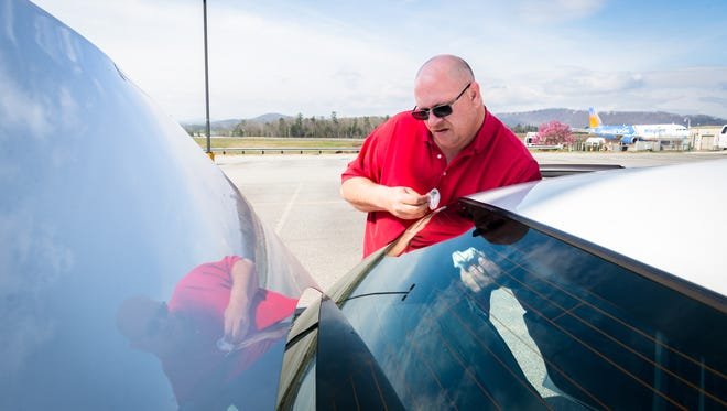 John Fuge, a taxi driver for American Cab Company, cleans his car at the Asheville airport, Monday, March 19, 2018. The airport has begun charging taxi drivers a fee each time they enter, a rule which the rideshare service, Uber has refused to comply with.